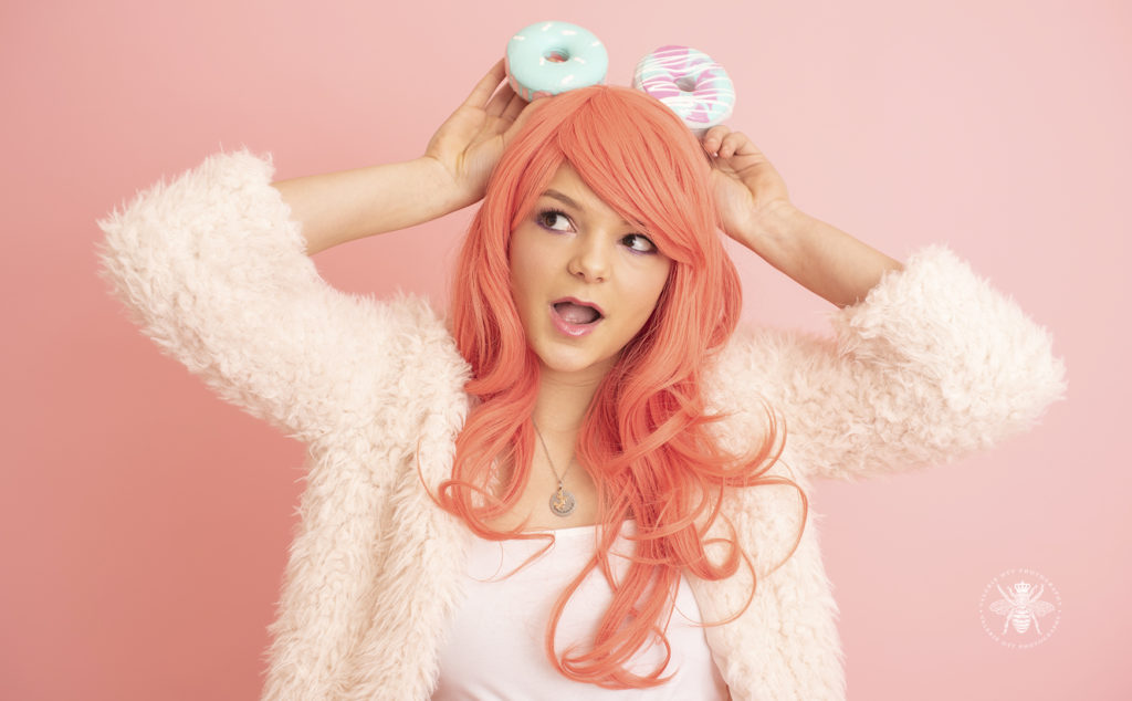 senior girl poses with foam donuts and pink colored hair in front of a pastel pink background