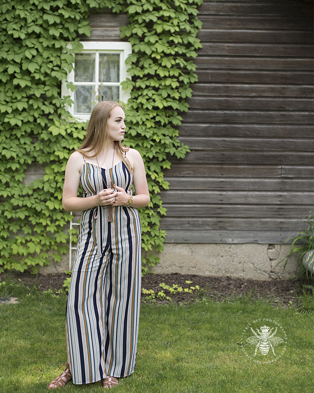 senior girl wears vintage striped jumpsuit and poses in leaf covered wall