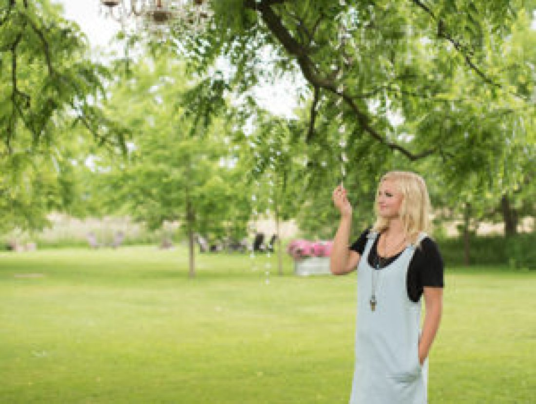 senior girl poses by trees in a field wearing a dress layered over a black top