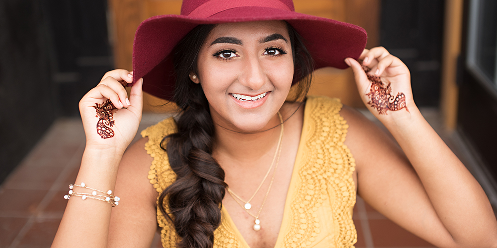 senior girl poses with red hat, wearing a yellow top with henna decorating her hands