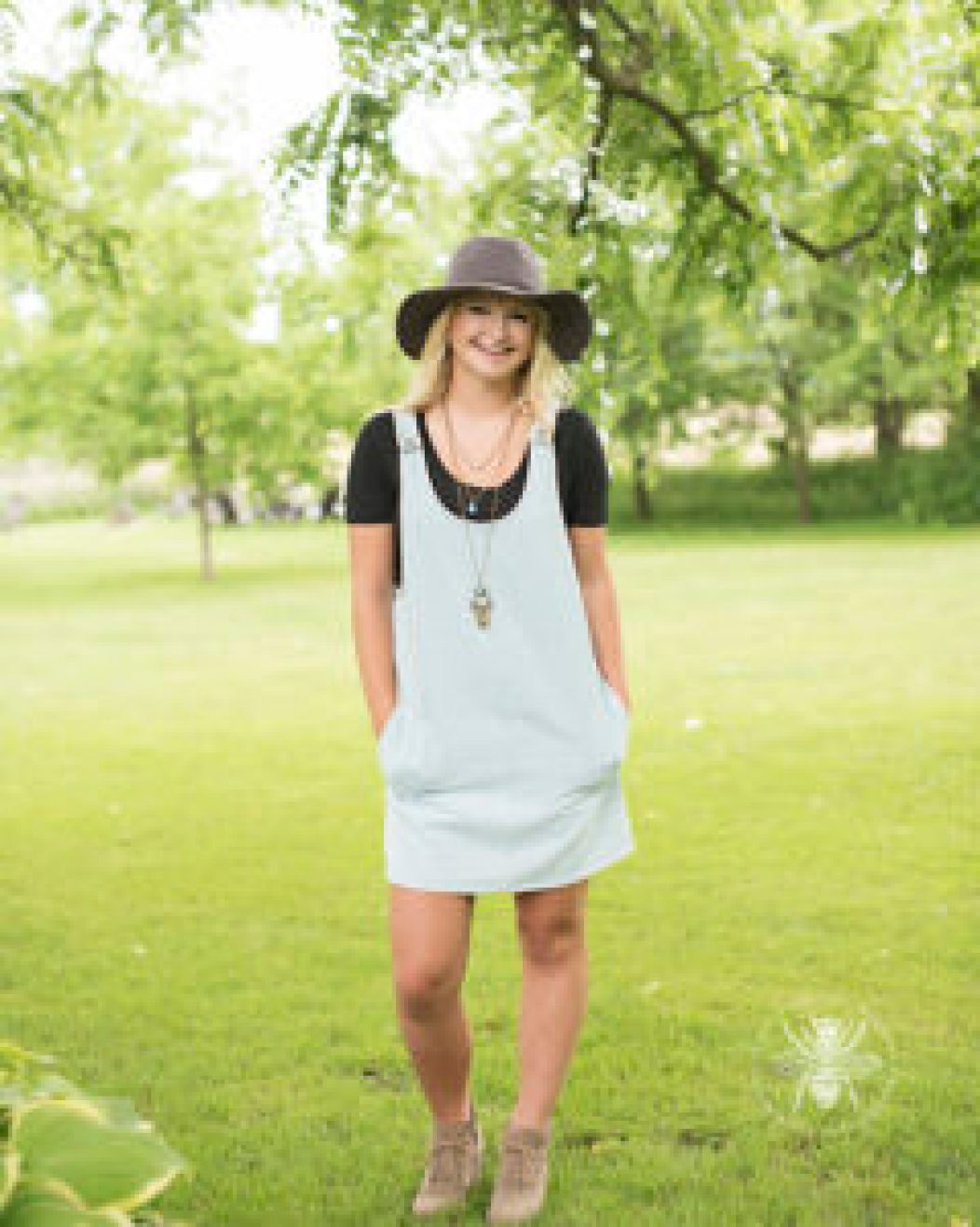senior girl poses in dress and hat in a field