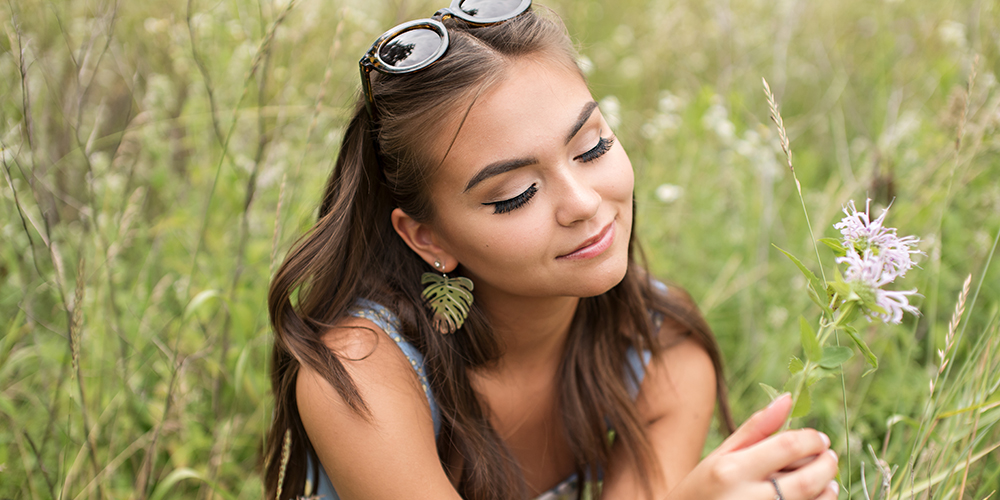 senior girl poses in field wearing light blue floral crop top, sunglasses, and leaf earrings.
