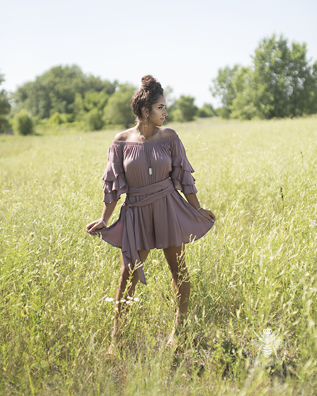 senior girl wears mauve dress and poses in a field