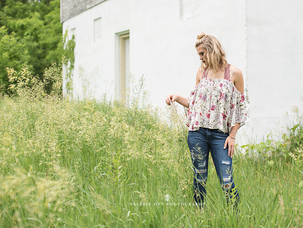 senior girl poses in a field in front of a white building wearing a floral top and jeans