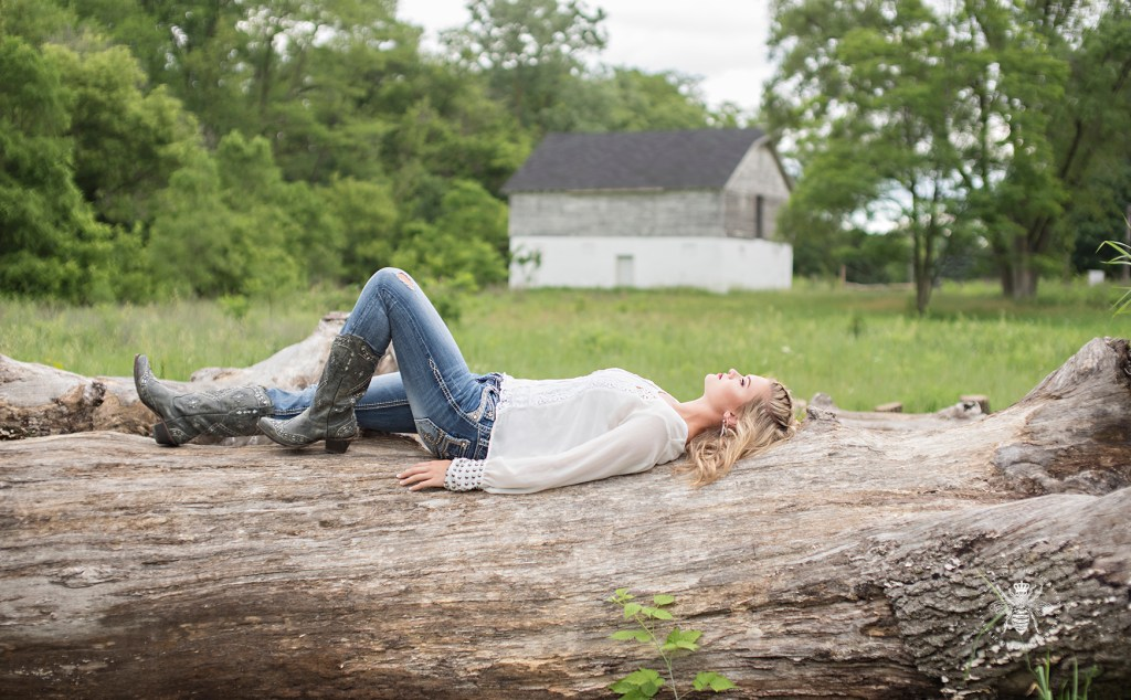 senior girl wears cowgirl boots, jeans, and a white top. She takes a nap on a fallen tree trunk.