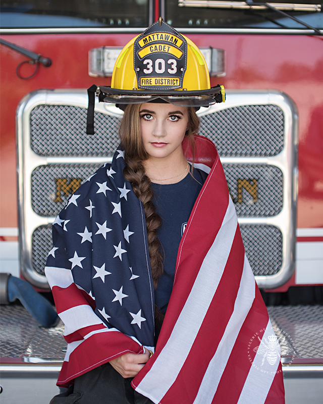 senior girl poses on Mattawan fire truck wearing her fire fighter uniform. She has an American flag wrapped around her body.