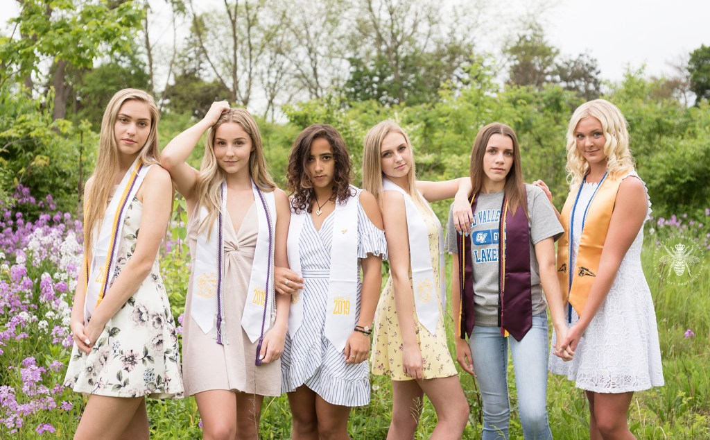 West Michigan high school graduates pose in a field wearing their cords.