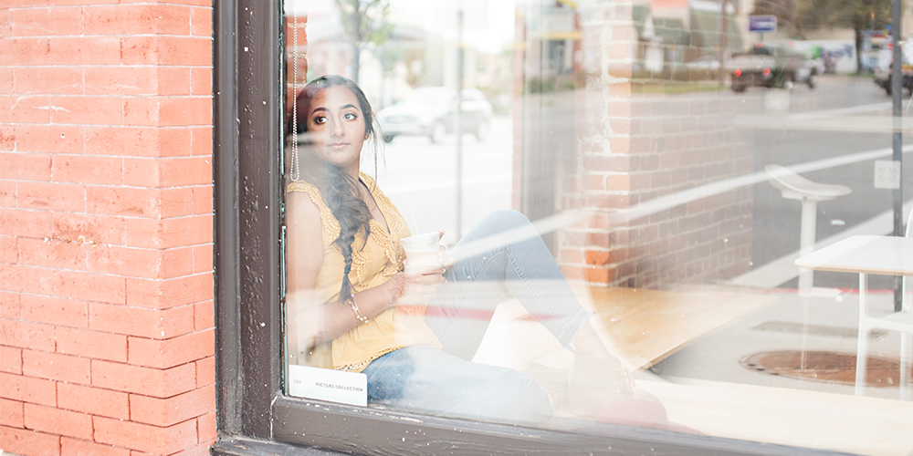 senior girl wears a yellow top and jeans and looks out the window of a coffee shop. She holds a cup of coffee in her hands.