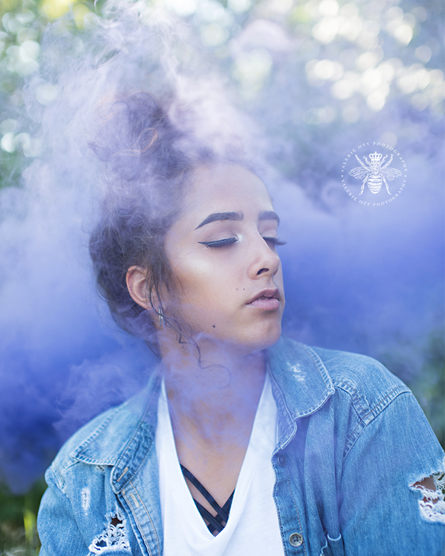 senior girl wears a denim jacket with her hair in a bun and is surrounded by purple smoke