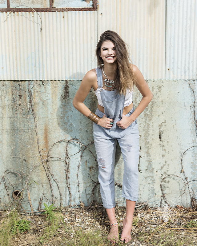 senior girl poses against an old wall. She is barefoot and wears overalls with a white crop top