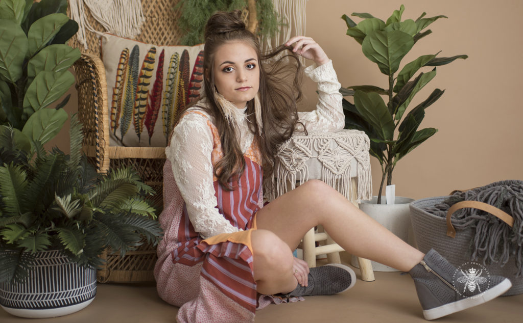 Mattawan senior girl poses in a studio with a vintage background with plants. She layers clothes and wears her hair half up, feather earrings, an orange, red and purple striped sundress layered over a white lace high neck top, and she wears gray wedge sneakers.