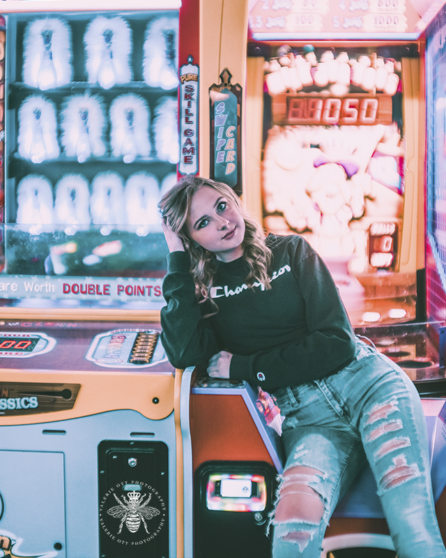 West Michigan senior girl poses by arcade games in Revel and Roll with the bright lights surrounding her. She wears ripped jeans and a Champion sweatshirt.