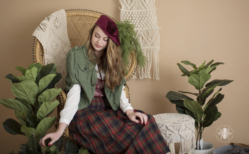 West Michigan senior girl poses in a studio with plants and a vintage background. Mix and match clothes, she wears a red beret, a green jacket, a red lace tank top layered over a white shirt, a green and red plaid skirt. She poses on a vintage chair.