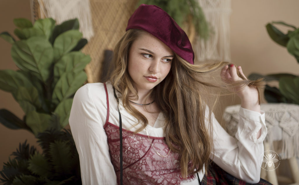 West Michigan senior girl poses playing with her hair. She wears a red beret and red lace tank top layered over a white shirt.