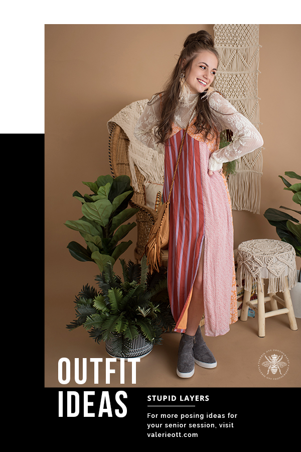 Mattawan senior girl poses in a studio with a vintage background with plants. She layers clothes and wears her hair half up, feather earrings, an orange, red and purple striped sundress layered over a white lace high neck top, and she wears gray wedge sneakers, and she wears a brown crossbody bag with fringe. Text reads: outfit ideas, stupid layers, for more posing ideas for your senior session, visit valerieott.com