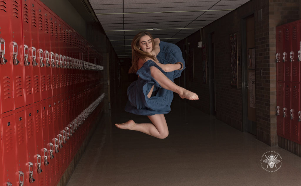 West Michigan senior girl is a dancer and poses in a school hallway surrounded by lockers. She wears a teal dress and is barefoot.
