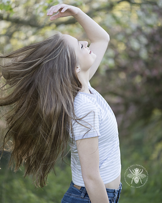 west michigan senior girl, a member of Valerie Ott's bee squad, throws her hair behind her and she wears a striped shirt