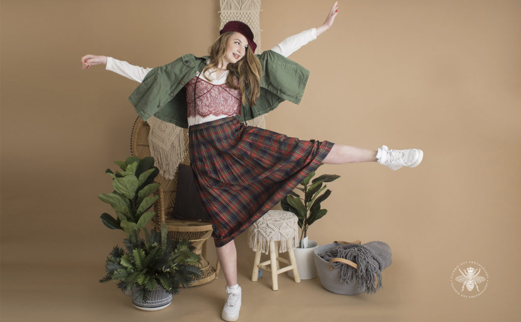West Michigan senior girl poses in a studio with plants and a vintage background. Mix and match clothes, she wears a red beret, a green jacket, a red lace tank top layered over a white shirt, a green and red plaid skirt, and white tennis shoes. She poses with her arms out and one leg in the air.