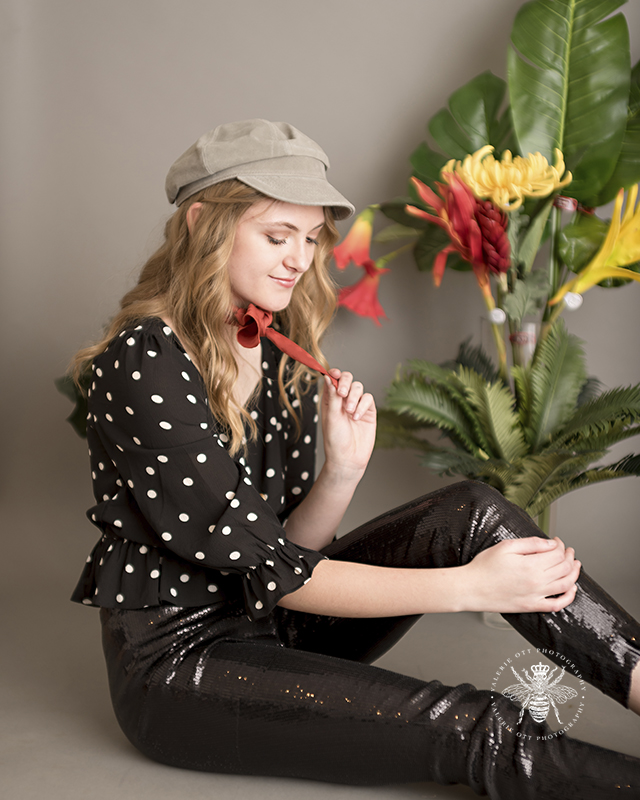 West Michigan senior session. Senior poses with red and yellow flowers in front of gray background. She wears a rust colored scarf around her neck, a tan hat, black sequin pants, and a black and white polka dot top.