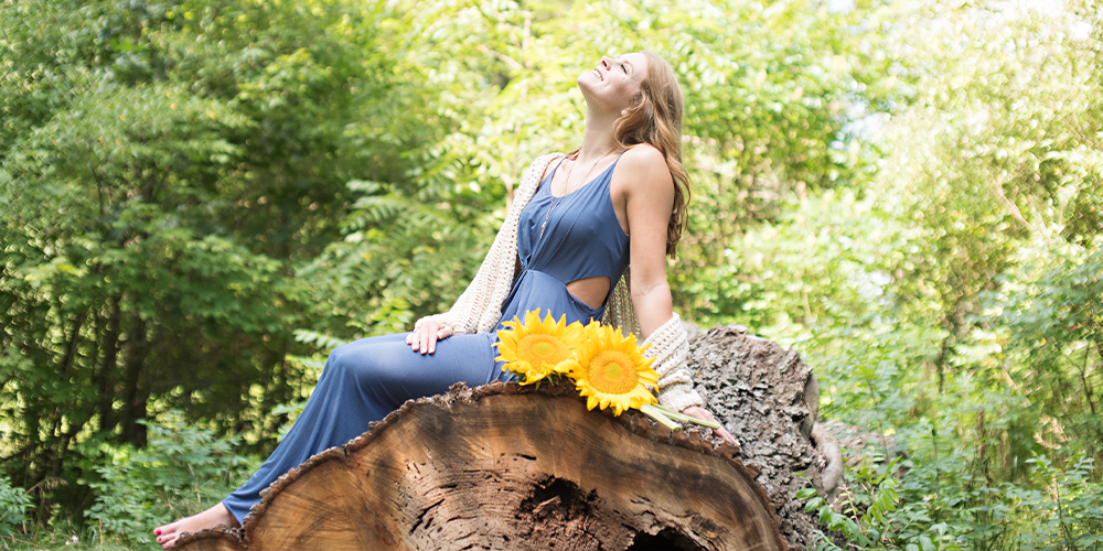 Portage Central senior poses on a fallen tree trunk with sunflowers. She wears a long blue dress with cutouts and a cardigan