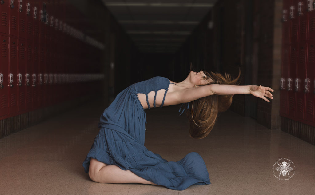 West Michigan senior girl dances in a school hallway surrounded by lockers. She wears a teal dress and is barefoot.