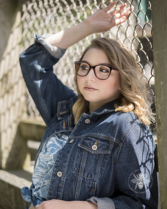 Gull lake senior girl poses in front of a chain link fence as one of her places during her senior session. She wears glasses and a denim jacket