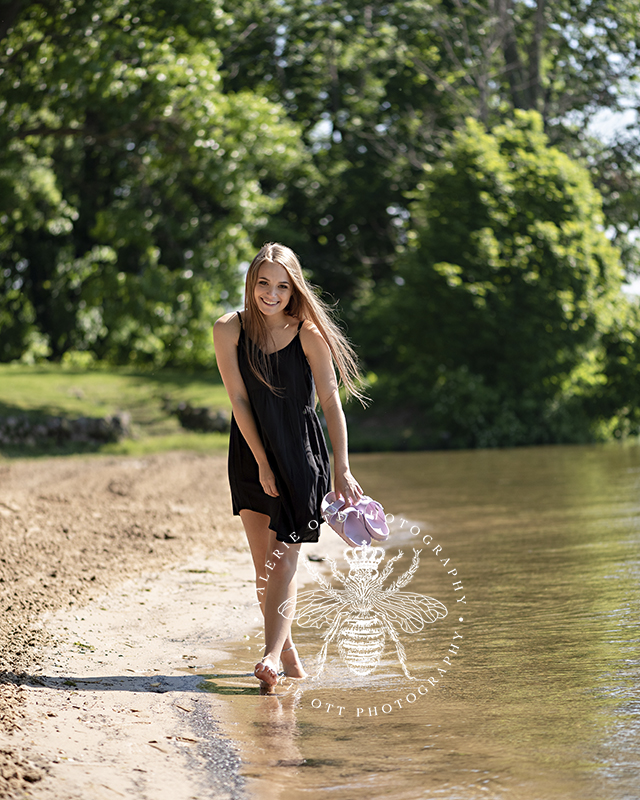 Mattawan senior session. Senior girl wears black dress and walks along the beach at Gun Lake near Kalamazoo, Michigan.