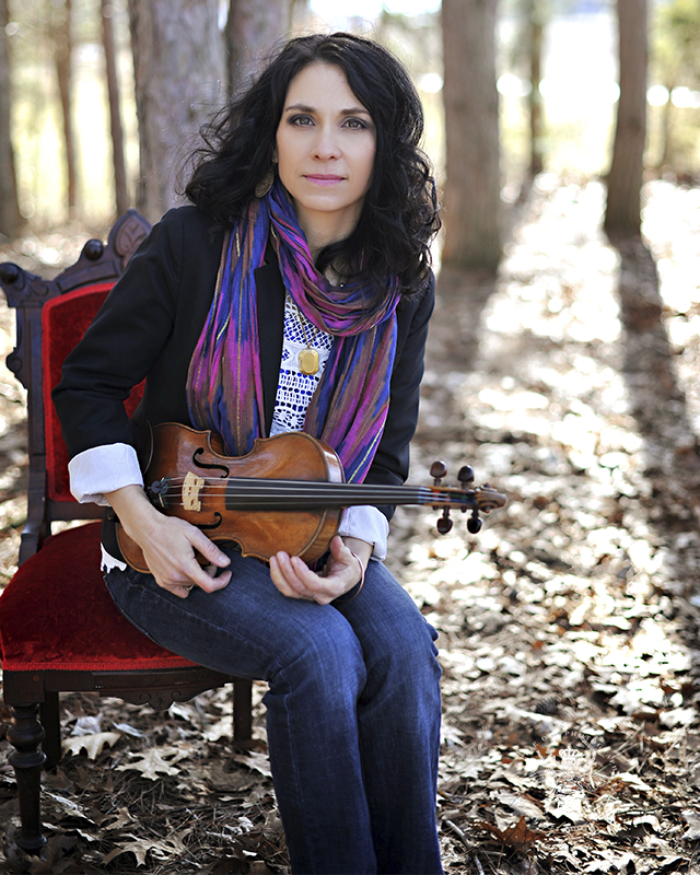 Photo session with Irish singer. She poses with her violin on a chair in the forest.