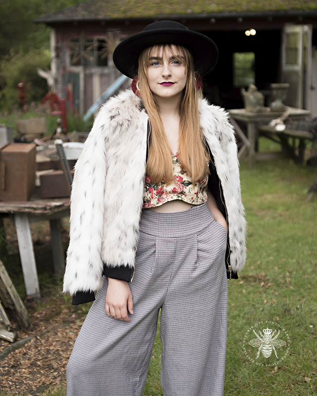 Mattawan senior girl poses in an abandoned location in West Michigan. She wears a unique outfit, gray wide leg pants, fur coat, floral top, and a black hat.
