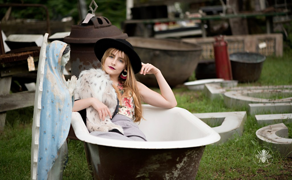 Mattawan senior girl poses in a bathtub in an abandoned location. She wears a hat, floral top, and a fur coat. This unique location is in West Michigan.