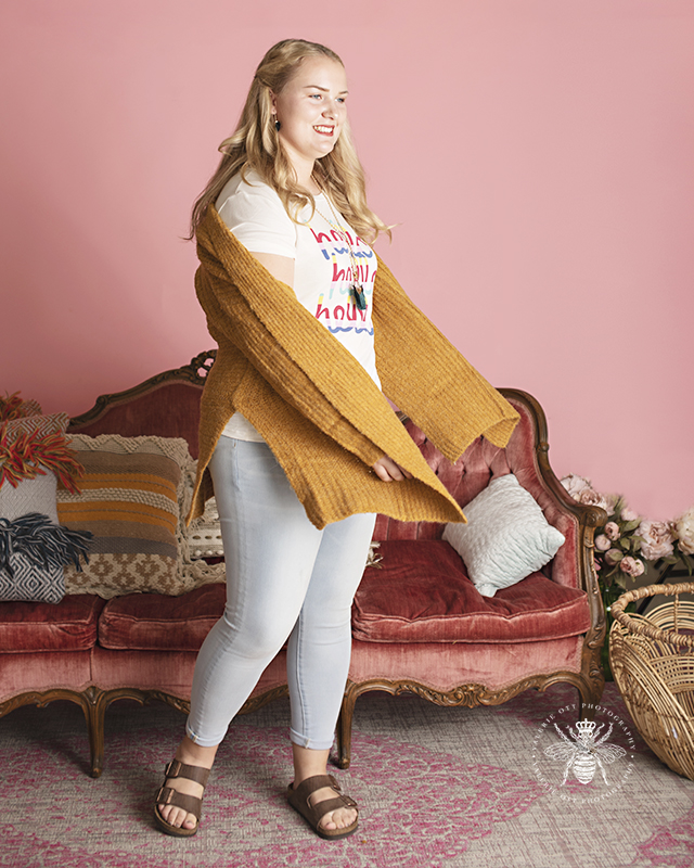 Model poses in front of a pink background and a vintage couch at Therapy Boutique in Portage, Michigan. She wears jeans, a graphic tee, a mustard yellow cardigan, and a long statement necklace.