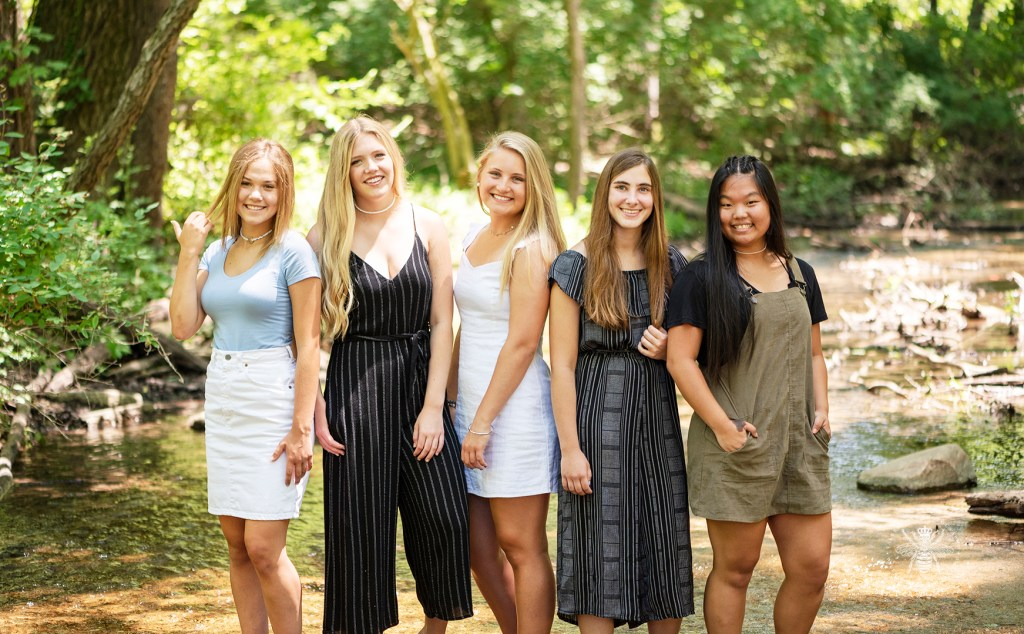 Kalamazoo Christian BFF session. Senior girls wear black, white, blue, and brown colors. They pose together in a forest in West Michigan.