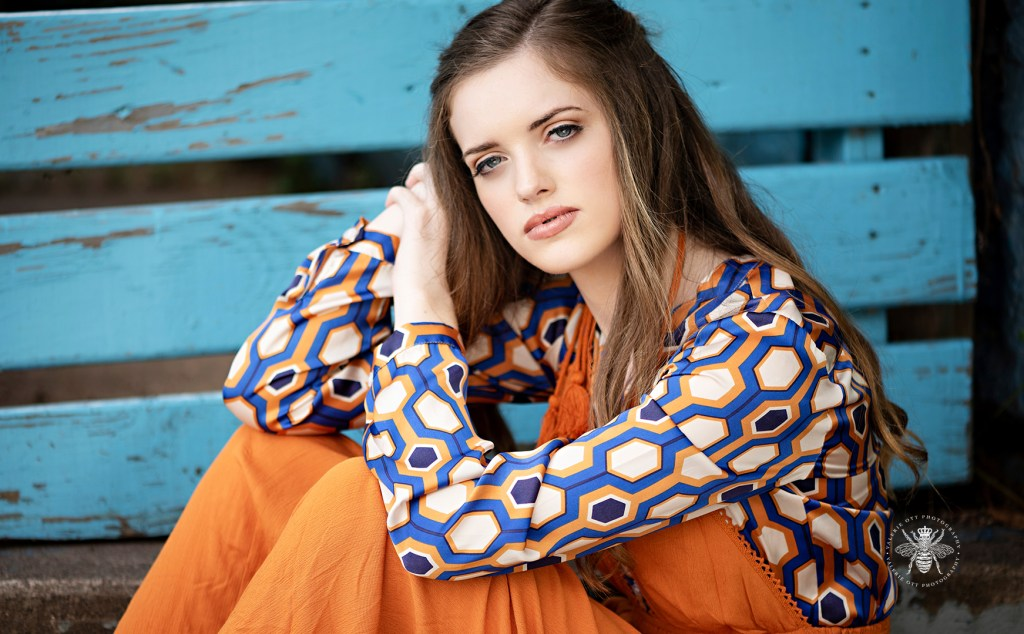 Model poses in front of a blue wall. She wears an orange dress layered over a retro blue and orange patterned top.