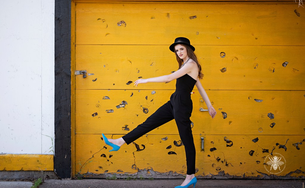 Senior girl poses in front of a yellow wall. She wears a black hat, black jumpsuit, and bright blue heels.