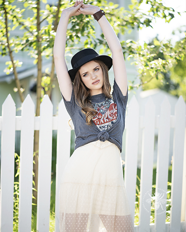 Model poses in front of a white picket fence. She lifts her arms above her head. She wears a t shirt knotted in front with a statement necklace layered over a white dress.