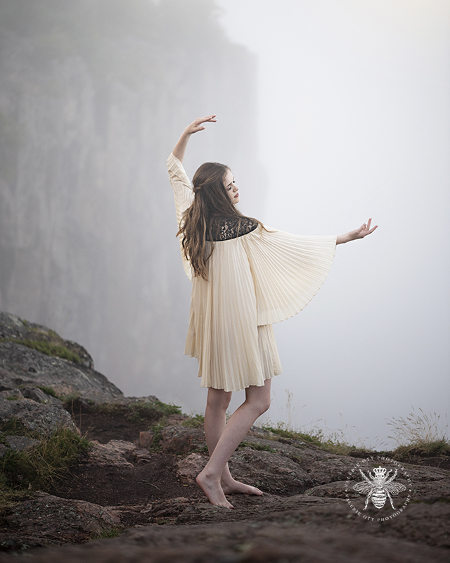 Senior girl poses standing on a foggy cliff. She wears a cream colored flowing dress.