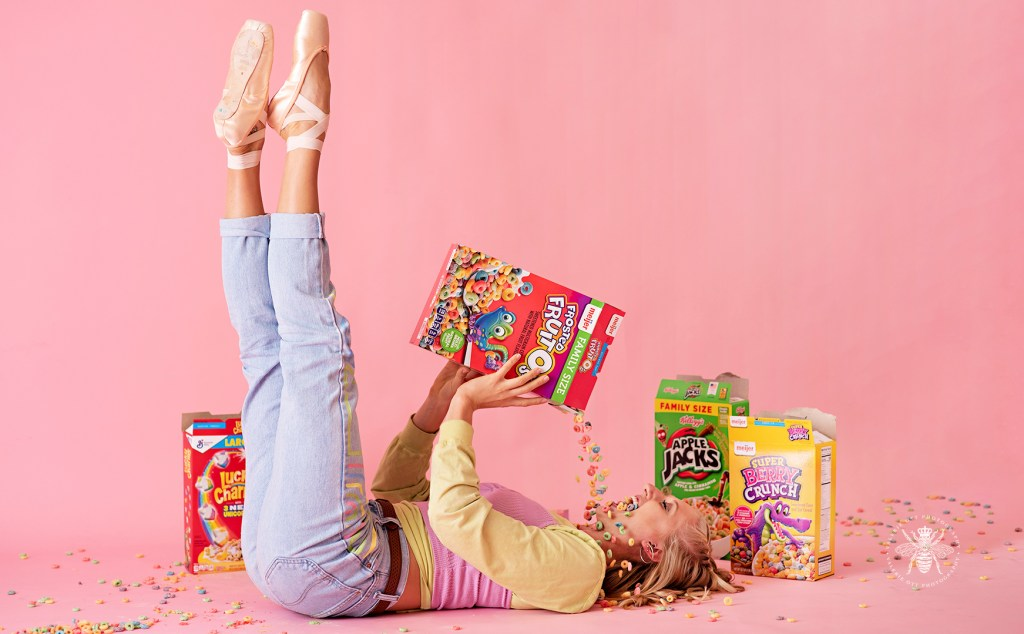 Western Michigan University dancer poses wearing ballet slippers and painted jeans. She pours cereal in her mouth in front of a pink background.