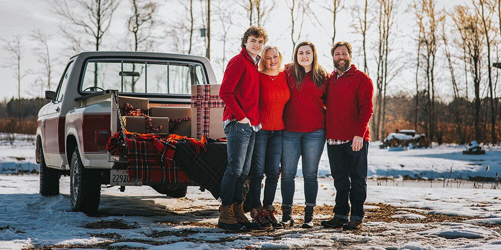 Mini Christmas family session at The Fields of Michigan. Family poses dressed in red in front of a truck with plaid blankets on the back