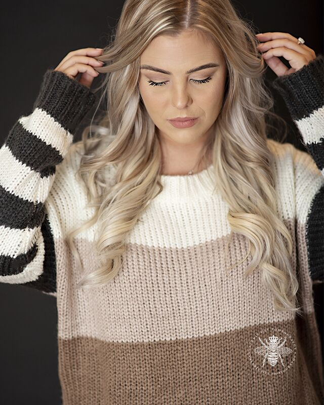 Western Michigan University senior pics. Senior poses in a studio in front of a gray background. She wears a neutral colored striped sweater.