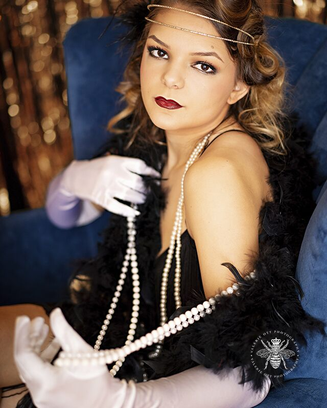 Mattawan senior poses for styled session in West Michigan. She wears her hair in pin curls, red lipstick, white gloves, pearl necklaces, a feather boa, and a flapper dress. She poses sitting in a blue velvet chair in front of a shimmering gold backdrop.