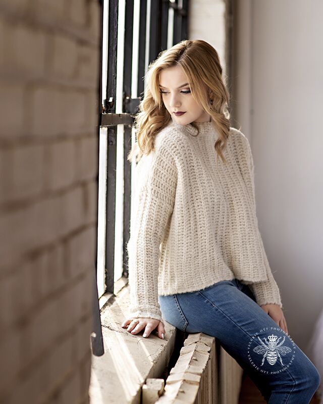Girl poses sitting on a windowsill. She wears jeans and a sweater.