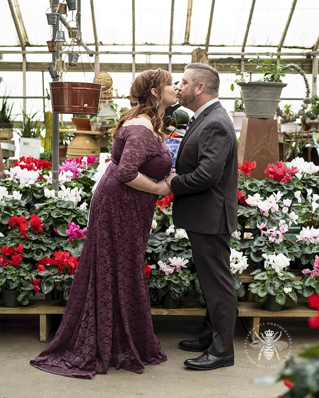 Courthouse wedding photographed in Kalamazoo, Michigan. The couple poses kissing in a greenhouse. The bride wears a long, purple lace dress with a silver belt around her waist. The groom wears a suit and patterned tie.