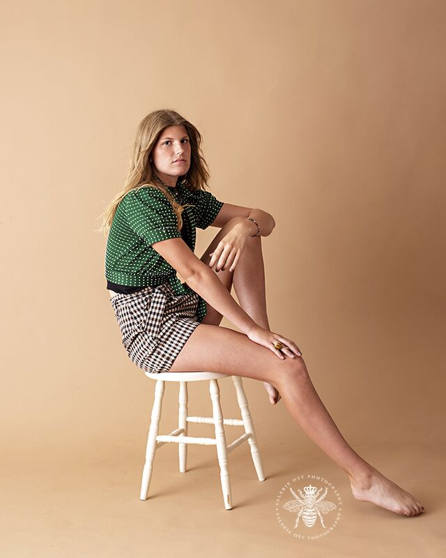 Model poses sitting on a stool in a studio for modeling headshots. She wears gingham shorts and a green polka dot top.
