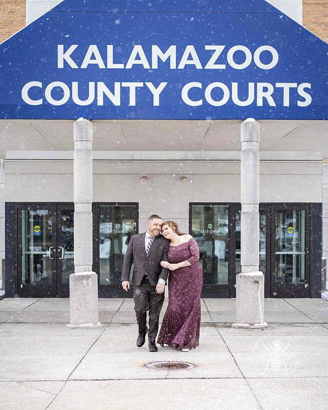 "Courthouse wedding in Kalamazoo, Michigan. Couple walks out of courthouse embracing and smiling. Snow falls around them and a sign above them reads, ""Kalamazoo County Courts."""
