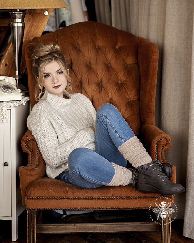 Gull Lake senior session. Senior poses on a brown velvet, vintage chair. She wears jeans, a sweater, socks, and boots. Her hair is in a messy bun.