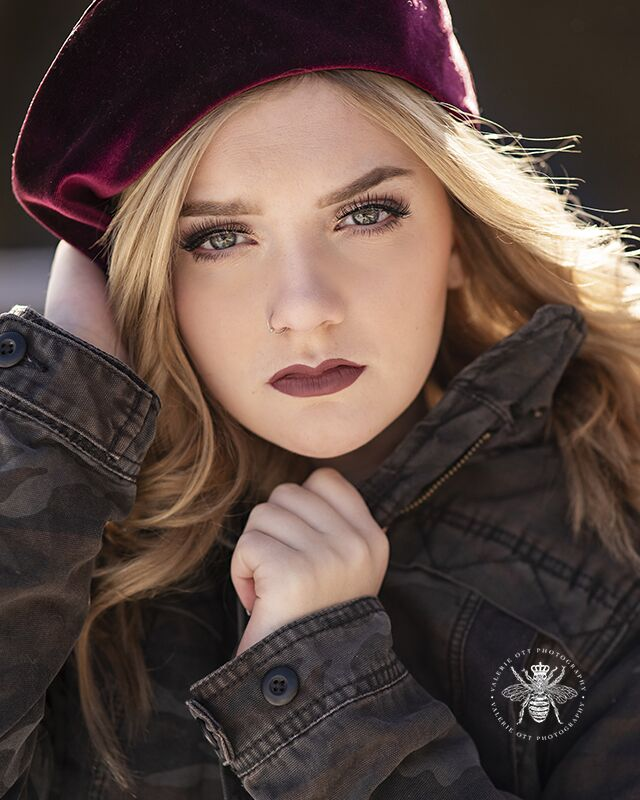 Girl poses wearing a velvet beret and a jacket.