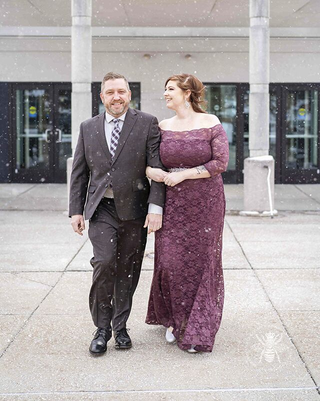 Courthouse wedding in Kalamazoo, Michigan. Couple walks out of courthouse embracing and smiling. Snow falls around them.