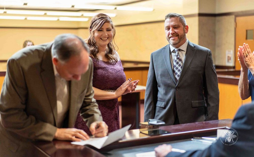 Courthouse wedding in Kalamazoo, Michigan. Couple smiles while documents are signed.