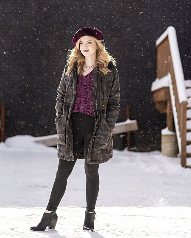 Girl poses wearing a camo jacket, purple sweater, black pants, heeled ankle boots, and a velvet beret. Her hands are in her pockets and snow falls around her.