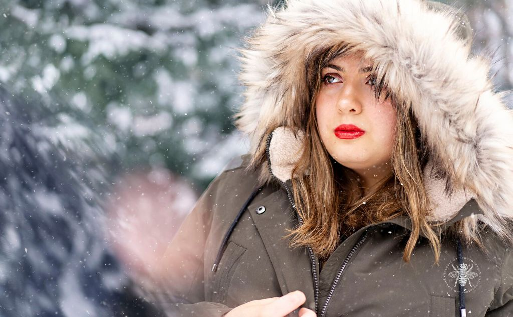 Girl poses in front of snow covered pine trees with snow falling around her. She wears a coat with a fur lined hood and red lipstick.